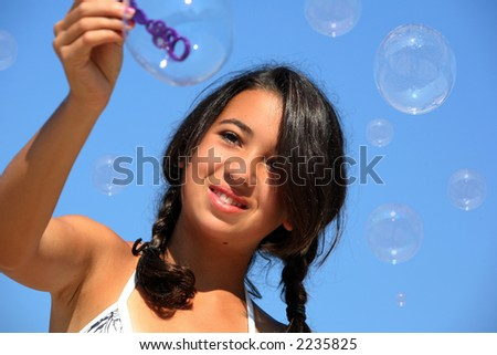 Happy girl playing with bubbles on the beach - stock photo