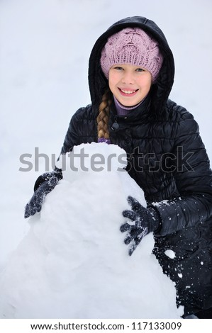Happy girl playing with snow and sculpts snowman. - stock photo