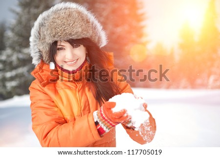Happy girl playing with snow in the winter landscape - stock photo