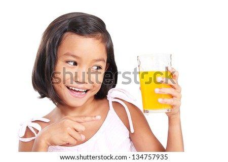 Happy girl pointing to a glass of orange juice.Isolated in white background.