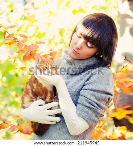 Happy girl portrait playing with her ginger cat, autumn outdoor.  - stock photo