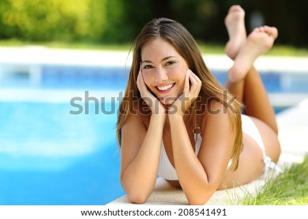 Happy girl posing wearing bikini on a pool side in summer vacations with a garden in the background        - stock photo