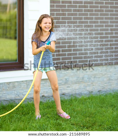 Happy girl pouring water from a hose on backyard - stock photo