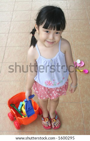 happy girl pulling beach playset - stock photo