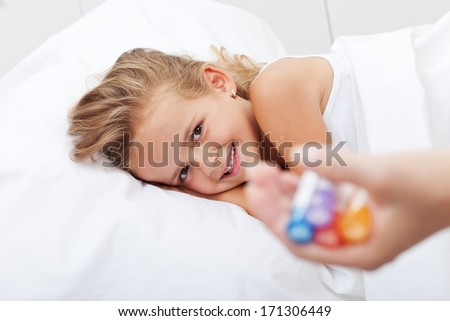 Happy girl recovering from illness with homeopathic medicine - held in woman hand - stock photo