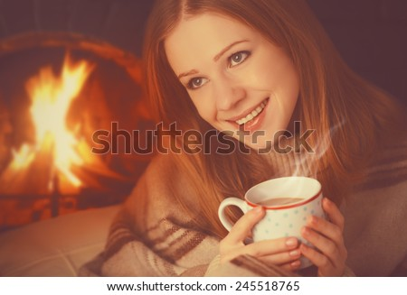 happy girl relax by the fireplace with a mug of warming tea, coffee in the winter - stock photo