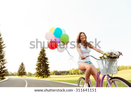 happy girl riding on a bicycle with flowers - stock photo