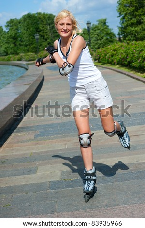 Happy girl roller-skating in the park at summer - stock photo