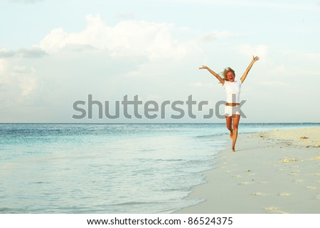 happy girl run along the ocean coast
