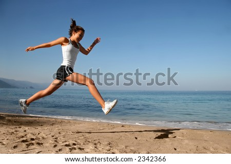 Happy girl running alone on the beach