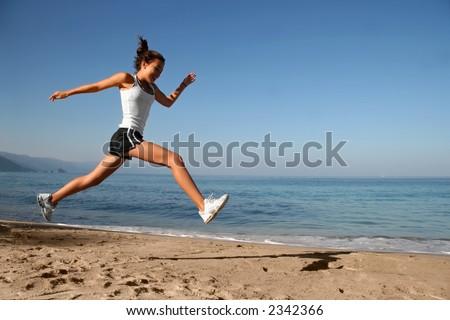 Happy girl running alone on the beach - stock photo