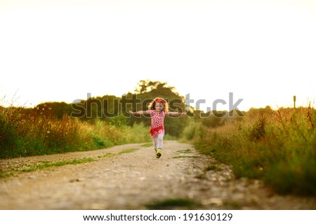 happy girl running at field road - stock photo
