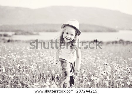 happy girl running in field of daisies - stock photo