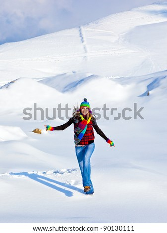 Happy girl running in the snow, teen outdoor winter activities, female having fun at Christmastime, woman wearing colorful clothes, freedom and nature joy concept - stock photo