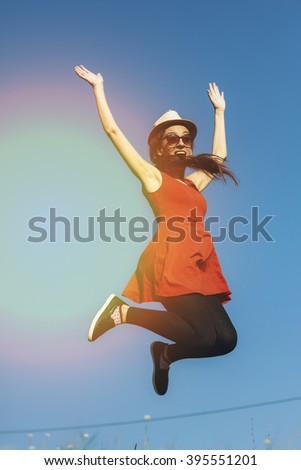 happy girl running jumping carefree with outstretched hands over green field and blue sky - stock photo