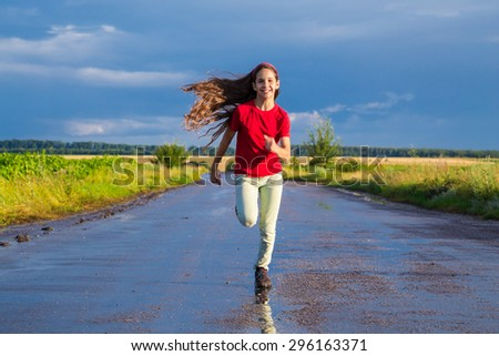 Happy girl running on wet road after rain - stock photo