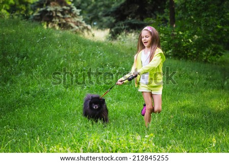 Happy girl running with her pomeranian doggy
