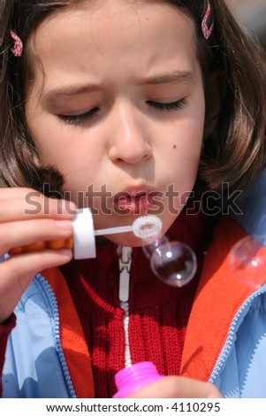 Happy girl's blowing funny bubbles