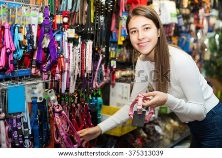 Happy girl selecting collars and leads in petshop - stock photo