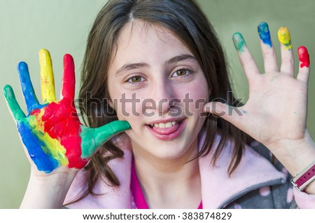 Happy girl showing her hands painted in bright colors. - stock photo