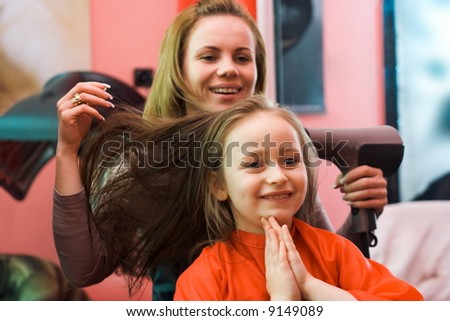 Happy girl sitting at the hair stylist, shes hair is being dried - stock photo