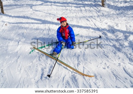 Happy girl sitting down on the snow learning skiing in the forest - stock photo