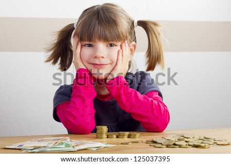 Happy girl sitting in front of a lot money - stock photo