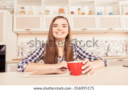 Happy girl sitting in the kitchen with tablet and a cup of coffee