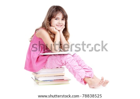 Happy girl sitting on books and reading a book