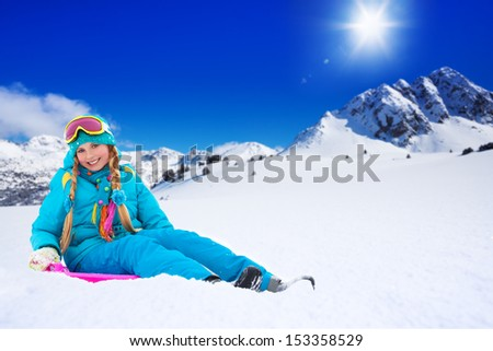 Happy girl sitting on sled, wearing ski mask, with mountains on background