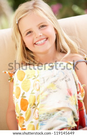 Happy Girl Sitting On Sofa - stock photo