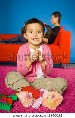 happy girl sitting on the carpet and playing blocks and  her busy (with laptop) mother on the sofa - stock photo
