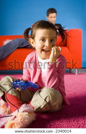 happy girl sitting on the carpet and playing video game and  her busy (with book) mother on the sofa - stock photo
