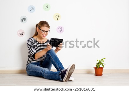 Happy girl sitting on the floor at home using tablet pc for online chatting or shopping. Young smiling female relaxing, surfing internet in her room.   - stock photo