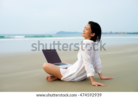 Happy girl sitting with laptop working at the beach