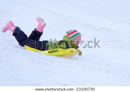 Happy Girl Sledding in Colorful Clothing - stock photo