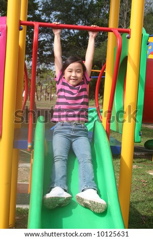 Happy girl sliding at the playground in the park