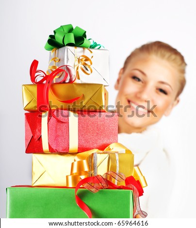 Happy girl smiling, holding colorful holiday presents & gift boxes as Christmas & new year ornament decoration isolated on white background - stock photo