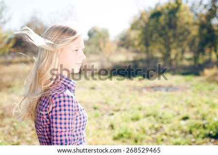 Happy girl standing in the field on sunny background - stock photo