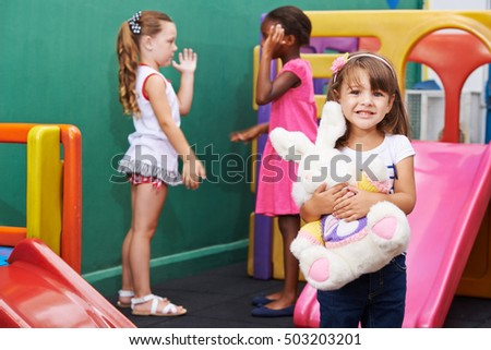 Happy girl standing with stuffed animal in a kindergarten