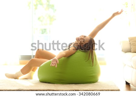 Happy girl stretching arms looking at camera and sitting on a pouf at home - stock photo