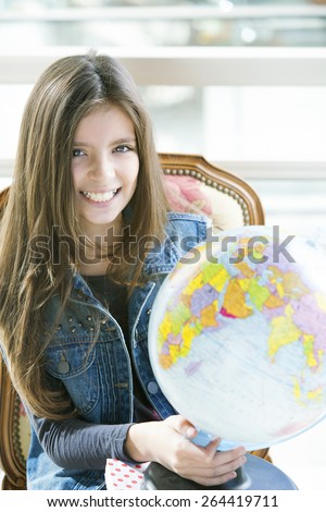 Happy girl studying with globe - stock photo