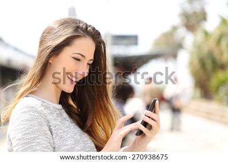 Happy girl texting on a smart phone in a train station while is waiting - stock photo