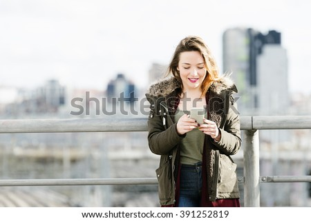 Happy girl texting on a smartphone in the city. - stock photo