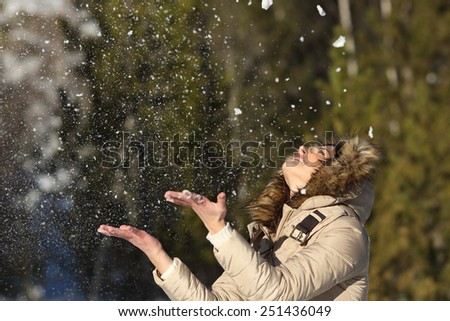 Happy girl throwing snow in the air on winter holidays in a forest in a sunny day - stock photo