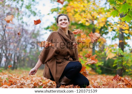 Happy girl throws maple leaves in autumn park - stock photo
