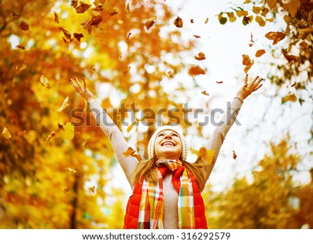 Happy girl throws up autumn leaves in the park for a walk outdoors - stock photo