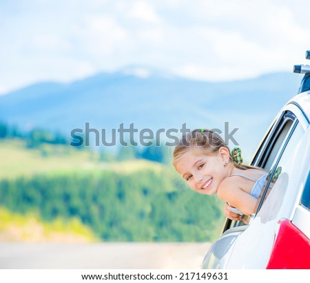 Happy girl travel by car in the mountains. Summer vacation concept - stock photo