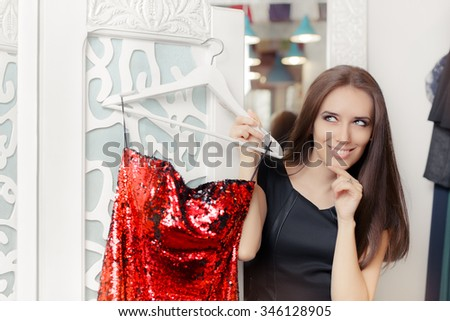 Happy Girl Trying on Red Party Dress in Dressing Room - Smiling fashion holding a clothes hanger with a fashionable garment  - stock photo