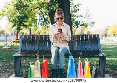 Happy girl using smart phone after holiday shopping - stock photo